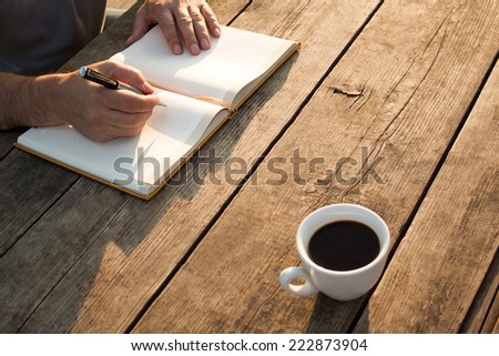 Man writing notes on wooden table on sunset. - stock photo