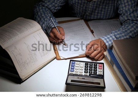 man writing notes while studying notes for exams. - stock photo