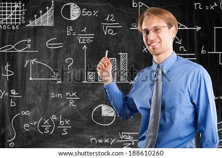 Man writing on a blackboard - stock photo