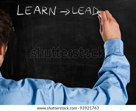 Man writing on a blackboard an educational concept - stock photo