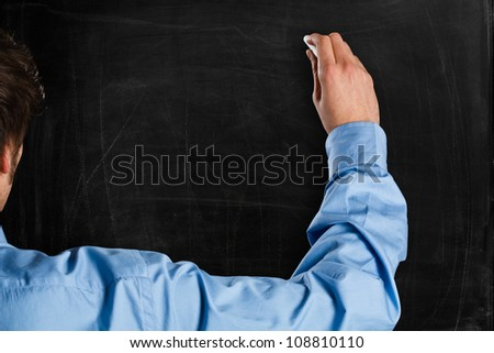 Man writing on a empty blackboard. You can add your own text - stock photo