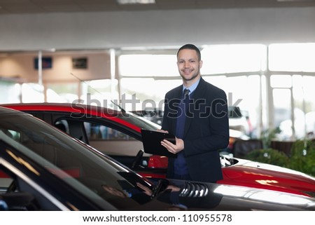 Man writing on a notepad beside a car in a garage - stock photo