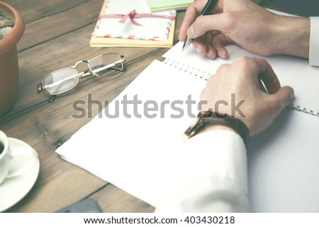 man writing on idea paper on wooden working table - stock photo