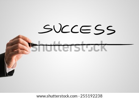 Man writing the word - SUCCESS - with a black marker pen from behind a virtual screen or interface on a light grey background with copyspace, close up view of the text and his hand. - stock photo