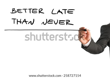 Man writing the words - Better late than never - with a black marker pen from behind a virtual screen or interface on a white background with copyspace, close up view of the text and his hand. - stock photo