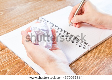 man writing with pen on notebook and crumpled paper in hand - stock photo