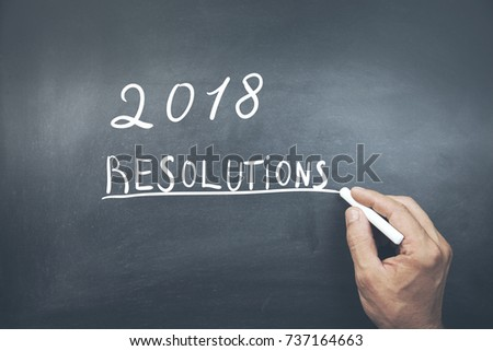 man written 2018 resolutions text on chalkboard
