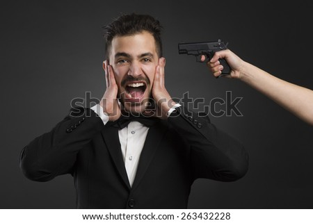 Man yelling with a weapon pointing on his head  - stock photo