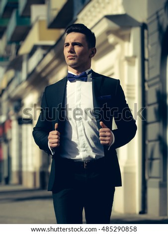 Man young handsome elegant in open suit coat with bow tie with serious look outdoor on urban background