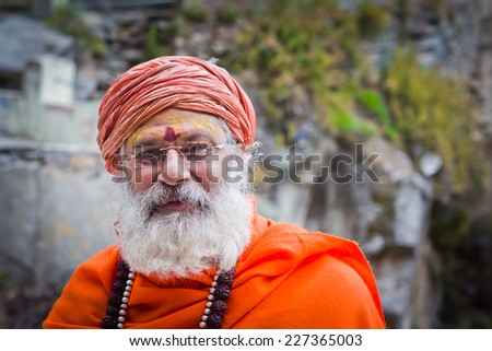 Mana village, India - October 1, 2014: A sadhu man in saffron clothes with smile on face.