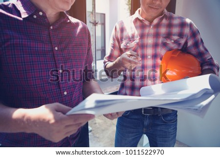 Management consulting engineers working construction site stock management consulting with engineers working at construction site and holding blueprint in his hand for management malvernweather Choice Image
