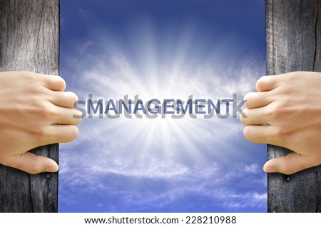 Management word floating and shining in the sky while two hands opening an old wooden door. - stock photo