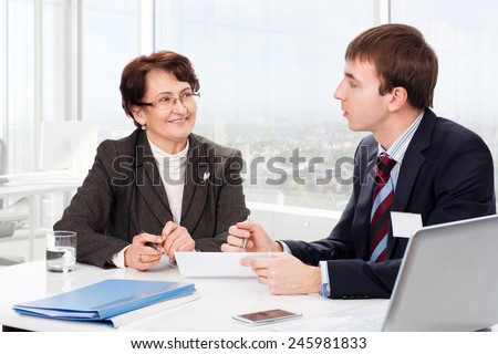 Manager advises the elderly woman in the office