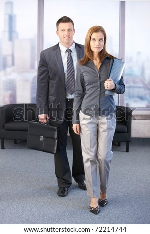 Manager and assistant going to business meeting, smiling.?
