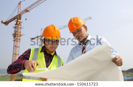 Manager builder on jobs site discussion stock photo royalty free manager and builder on the jobs site discussion looking blueprint under new building construction malvernweather Image collections