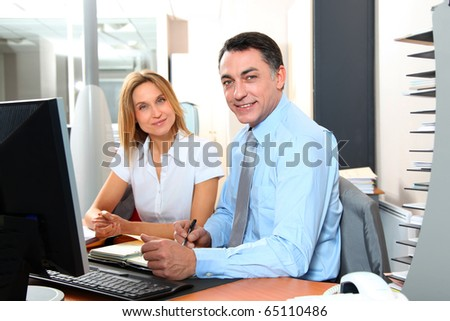 Manager and employee in front of computer in the office - stock photo