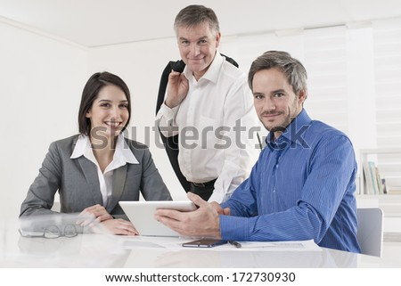 manager and his workteam at office looking at camera