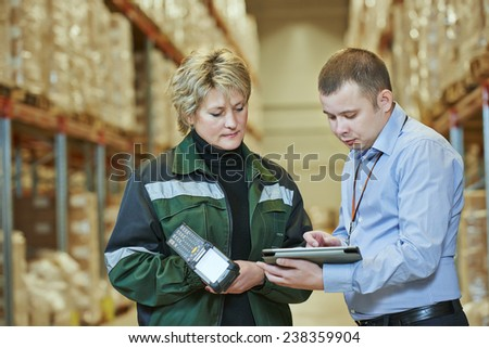 manager and worker in warehouse with bar code scanner - stock photo