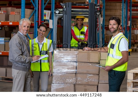 Manager and workers are posing and looking the camera in a warehouse
