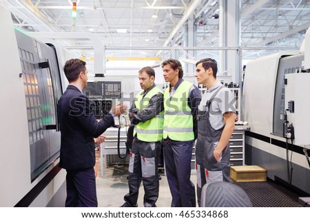 Manager and workers at plant near CNC machines