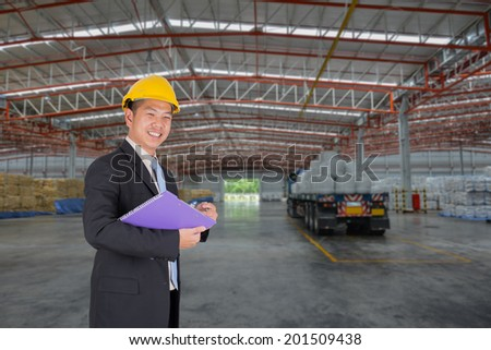 Manager asian business at happy complete job in warehouse - stock photo