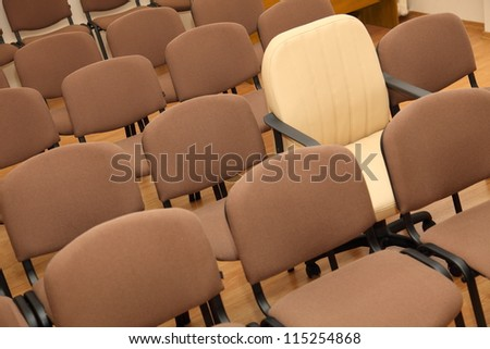 Manager chair stands out among the rows of ordinary office chairs - stock photo