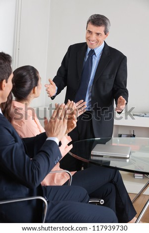 Manager clapping hands for consultant after a presentation in the office - stock photo