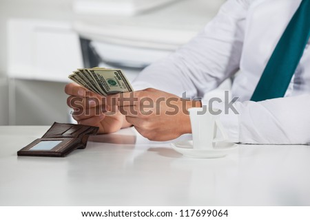 Manager counting a bunch of dollar bills in his office - stock photo