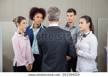 Manager discussing with serious employees while standing in call center - stock photo