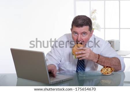 manager eating unhealthy food at work place - stock photo