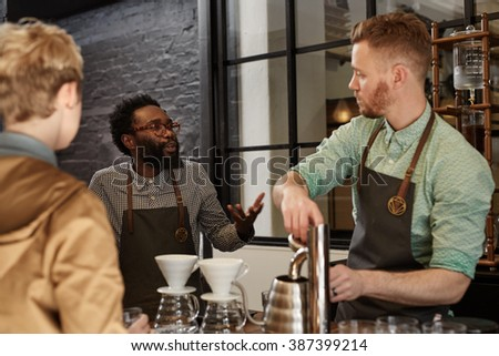 Manager explaining something to a staff member in coffee shop - stock photo