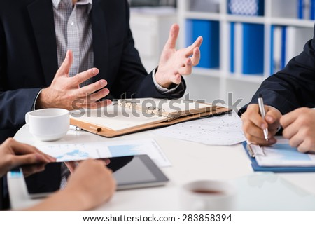 Manager explaining something to his colleagues at meeting