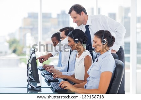 Manager explaining something to his employee in a call centre - stock photo