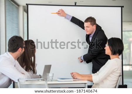 Manager giving a presentation on whiteboard background - stock photo