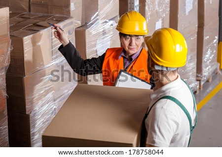 Manager giving worker instruction about loads storage in warehouse - stock photo