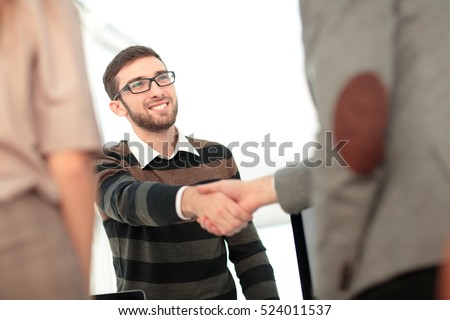 Manager greeting new employee and smiling in office