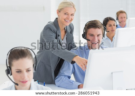 Manager helping call centre employee in the office