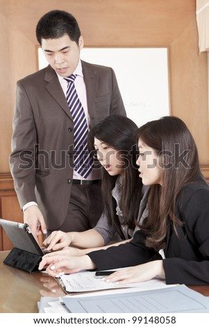 Manager helping his subordinate in the office - stock photo