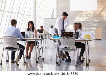 Manager Helping Staff In Busy Office Environment - stock photo