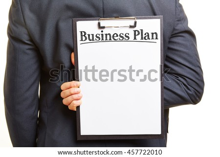 Manager holding business plan on clipboard behind his back - stock photo