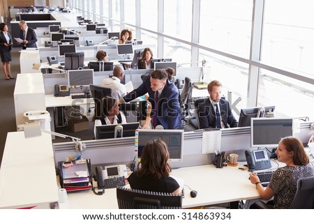 Manager in discussion with coworker in an open plan office - stock photo
