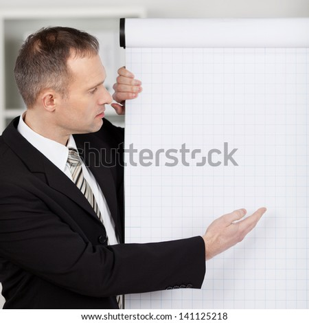 Manager in office pointing with index finger to empty flipchart - stock photo