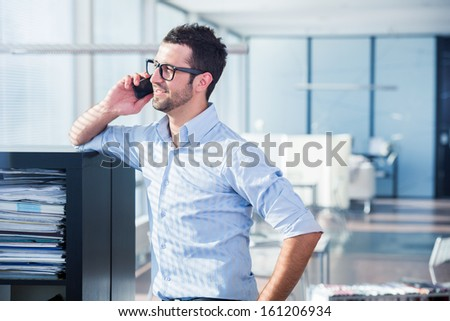 Manager in office talking to a mobile phone - stock photo