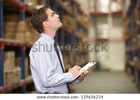 Manager In Warehouse With Clipboard - stock photo