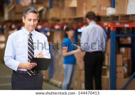 Manager In Warehouse Writing On Clipboard