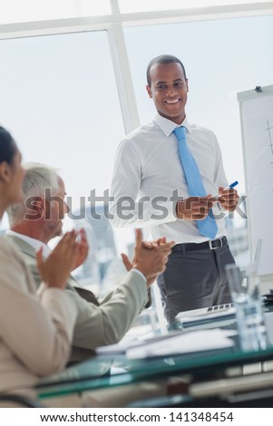 Manager is being applauded by colleagues at the end of a presentation - stock photo