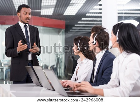 Manager is explaining something to employees in a call centre