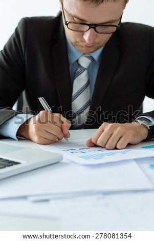 Manager making notes in financial document - stock photo