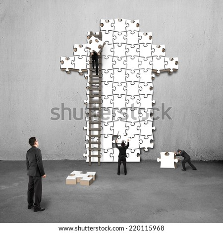 manager oversee teamwork for puzzles in arrow shape on concrete wall - stock photo