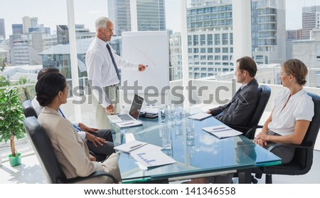 Manager pointing at a chart during a meeting with all the staff - stock photo